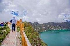 Jeune homme marchant dans la frontière avec une balustrade en bois de segurity, avec une belle vue de la caldeira de lac Quilotoa Photos stock
