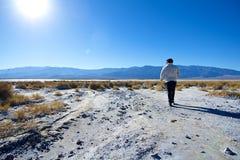 Jeune homme marchant par la terre stérile Image stock