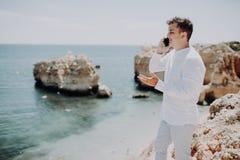 Jeune homme marchant sur la plage près de la mer, ayant un appel téléphonique avec son ami sur le fond d'océan image libre de droits