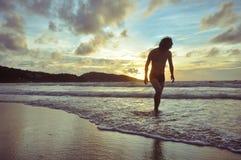 Jeune homme marchant sur la plage quand coucher du soleil Photographie stock