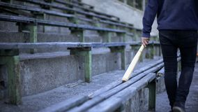 Jeune homme marchant sur la tribune de stade avec la batte de baseball, bande de la jeunesse, vandalisme images libres de droits