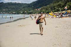 Jeune homme marchant sur le bord de l'océan Photographie stock
