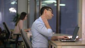 Jeune homme massant le cou engourdi, effets de travail sédentaire, problèmes avec la posture clips vidéos