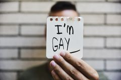 Jeune homme me montrant à une note avec le texte suis gai photos stock