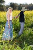 Jeune homme menant son amie par la graine de colza Images stock
