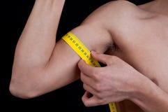 Jeune homme mesurant son bras Images libres de droits