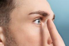 Jeune homme mettant le verre de contact dans son oeil image libre de droits