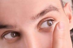 Jeune homme mettant le verre de contact dans son oeil photos stock
