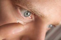 Jeune homme mettant le verre de contact dans son oeil photographie stock libre de droits