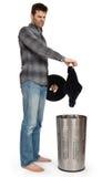Jeune homme mettant les chaussettes sales dans un panier de blanchisserie Image libre de droits