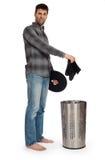 Jeune homme mettant les chaussettes sales dans un panier de blanchisserie Photographie stock