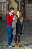 Jeune homme mettant un manteau sur les épaules de son amie Photographie stock libre de droits