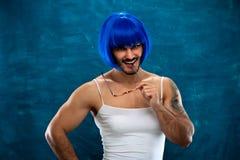 Jeune homme mignon portant la perruque bleue et le tissu femelle photo stock