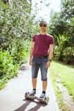Jeune homme moderne dans des shorts de denim et des tours de T-shirt de Bourgogne autour de la ville sur le hoverboard images libres de droits