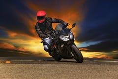 Jeune homme montant la grande moto de vélo sur des routes goudronnées Photo libre de droits