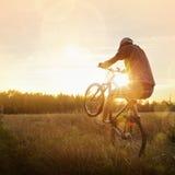 Jeune homme montant un vélo au coucher du soleil Image stock