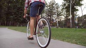 Jeune homme montant une bicyclette de vintage à la route de parc Recyclage sportif de type extérieur Mode de vie actif sain Angle Images libres de droits