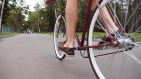 Jeune homme montant une bicyclette de vintage à la route de parc Recyclage sportif de type extérieur Mode de vie actif sain Angle Photos stock