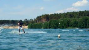 Jeune homme montant Wakeboard sur le lac Regards au cascade d'embarquement de sillage de formation de caméra banque de vidéos