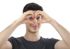 Jeune homme montrant la forme de coeur sur sa main dans une fin vers le haut de portrait Photo stock