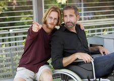 Jeune homme montrant quelque chose équiper dans le fauteuil roulant Image libre de droits