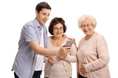 Jeune homme montrant quelque chose au téléphone à deux femmes agées Photographie stock libre de droits