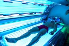 Jeune homme musculaire au solarium dans le salon de beauté Image libre de droits