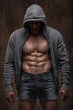Jeune homme musculaire avec la veste ouverte indiquant le coffre et l'ABS musculaires Photo stock