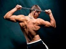 Jeune homme musculaire avec un réseau d'isolement sur l'obscurité Image libre de droits