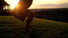 Jeune homme musculaire dans le dessus de réservoir faisant des postures accroupies à clips vidéos