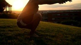 Jeune homme musculaire dans le dessus de réservoir faisant des postures accroupies à banque de vidéos