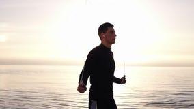 Jeune homme musculaire grand s'exerçant avec la corde à sauter au bord de la mer Jeune homme occupé dans le sport établissant deh banque de vidéos