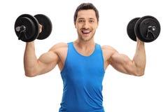Jeune homme musculaire s'exerçant avec des haltères photographie stock libre de droits