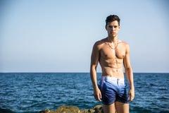 Jeune homme musculaire sans chemise contre le ciel Photos libres de droits