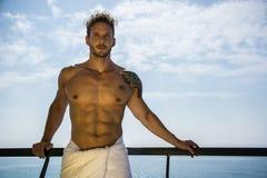 Jeune homme musculaire se penchant sur la main-balustrade sur le bateau de croisière photos stock