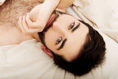 Jeune homme musculaire se situant dans le lit Image stock