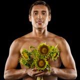 Jeune homme musculaire sexy avec un bouquet des fleurs images stock