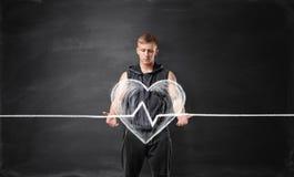 Jeune homme musculeux tenant le grand coeur battant dessiné sur le fond d'un tableau noir Images stock