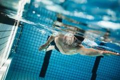 Jeune homme nageant le rampement avant dans une piscine photo stock