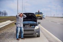 Jeune homme nerveux près de voiture cassée sur la route photos libres de droits