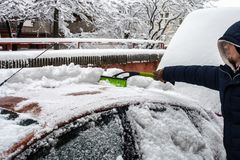 Jeune homme nettoyant sa voiture de la neige avec la brosse images libres de droits