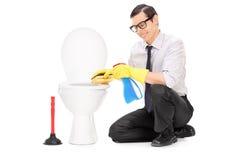 Jeune homme nettoyant une cuvette des toilettes avec une éponge Images stock