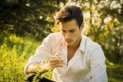 Jeune homme nostalgique rêvant en parc photo libre de droits