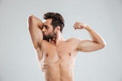 Jeune homme nu beau montrant et embrassant son biceps Photo stock