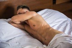 Jeune homme nu sexy sur le lit Photo stock