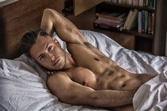 Jeune homme nu sexy sur le lit Photographie stock libre de droits