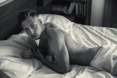 Jeune homme nu sexy sur le lit Image stock