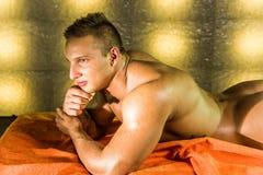 Jeune homme nu sexy sur le lit Photos stock