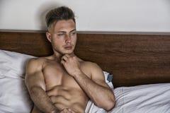 Jeune homme nu sexy sur le lit Photos libres de droits