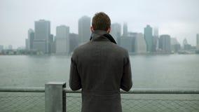 Jeune homme observant à Manhattan tout en se tenant près du fleuve Hudson banque de vidéos